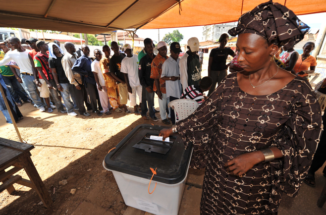 A woman casts her vote at a polling stat